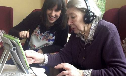 The artist Claire Ford using an iPad to inspire creativity in a woman with dementia